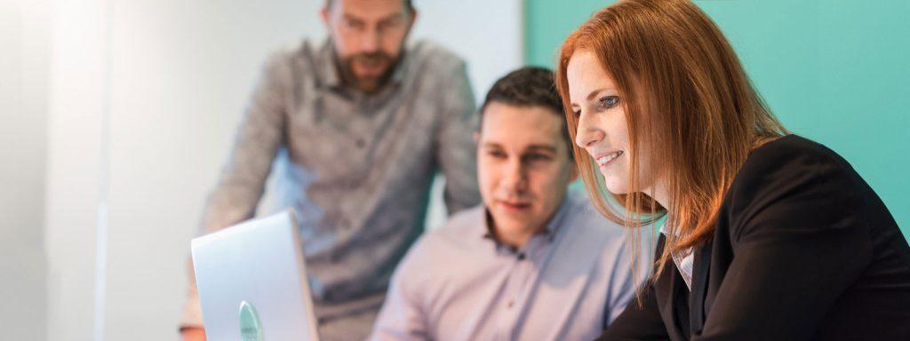En kvinna och två män tittar på en laptop, Advectas