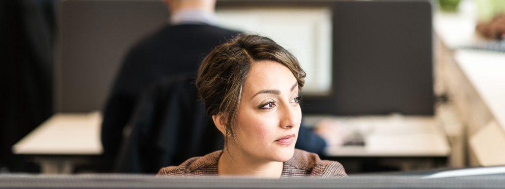 Kvinna i kontorsmiljö tittar drömmande åt höger, Advectas