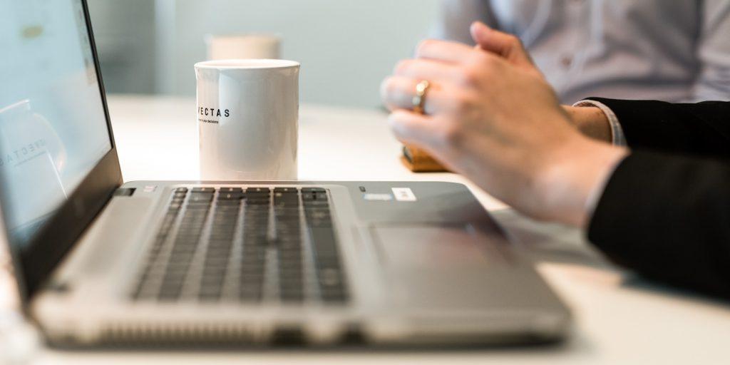 Närbild på en laptop, en mugg och händer
