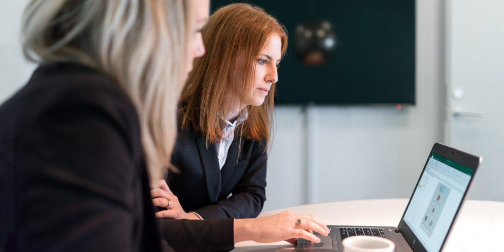 Två kvinnor i svarta kläder tittar på en laptop