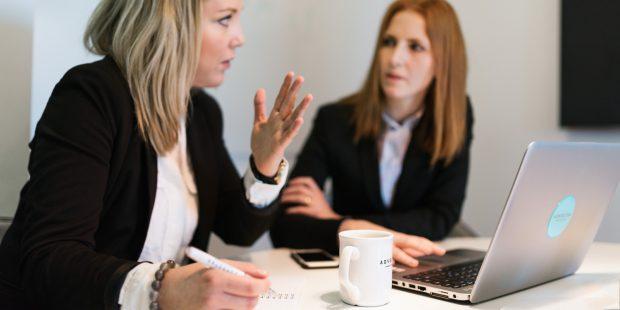Två stycken kvinnor har möte framför en laptop