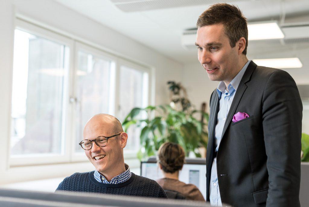 Två män står framför en datorskärm och skrattar